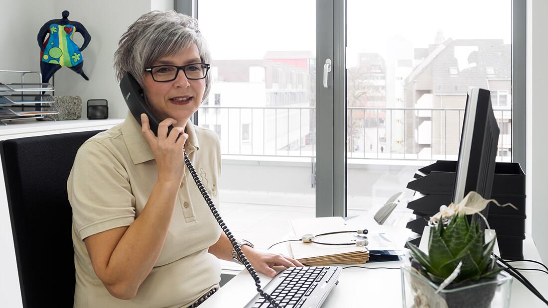Eine Mitarbeiterin am Telefon der Praxis - Frauenarzt Völklingen - Gemeinschaftspraxis Dr. Wagner, Dr. Hefti, Dr. Siebenborn, Dr. Zwank-Koebnik